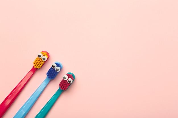 Детские зубные щетки разных цветов на розовом