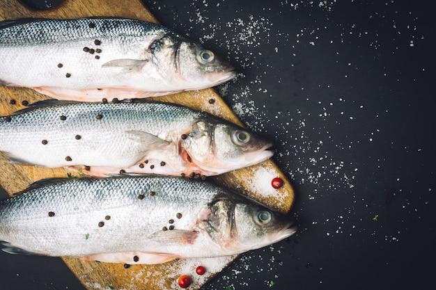 新鮮な生のスズキの魚、スパイス、塩、レモン、タイム、