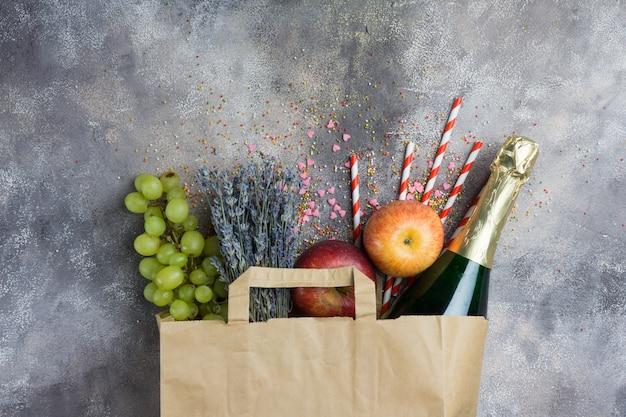 灰色のコンクリート背景にペーパークラフトパックにワイン、果物、花(パーティーやピクニックに設定)。上面図。