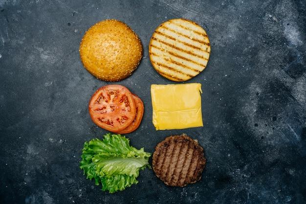 自家製バーガーの組成(レシピ)。暗い背景の古典的なハンバーガーの製品。