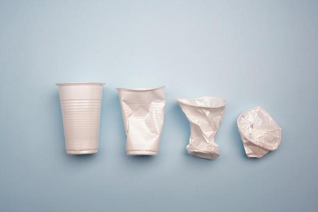 明るい青色の背景にしわくちゃのプラスチックカップ。クリエイティブなミニマルコンセプト