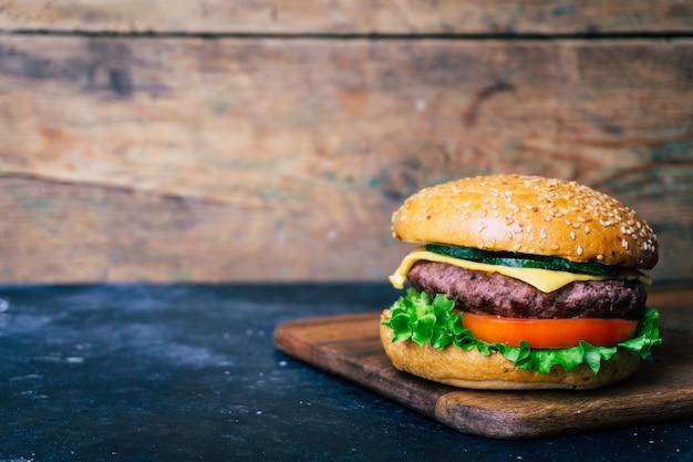 木製の背景に牛肉と自家製バーガー(チーズバーガー)。古典的な自家製バーガー。