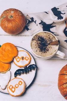 Хэллоуин фон с домашним хэллоуин печенье и тыквы на деревянный стол.