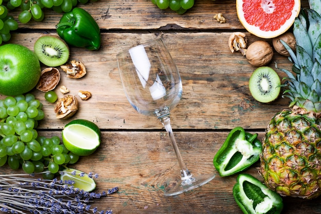 ワインのコンセプト。緑のブドウ、グレープフルーツ、古い木製のテーブルの他の果物と若い白バイオワインのガラス