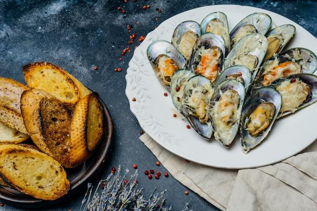 白い皿にパルメザンチーズとガーリッククルトンと焼きムール貝