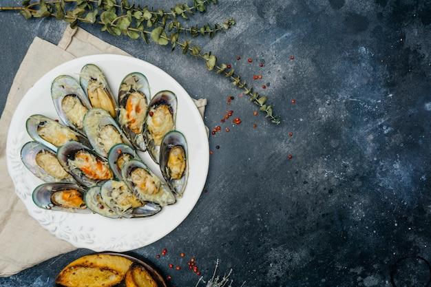 暗い背景に白い皿にパルメザンチーズとニンニクのクルトンと焼きムール貝。コピースペース。