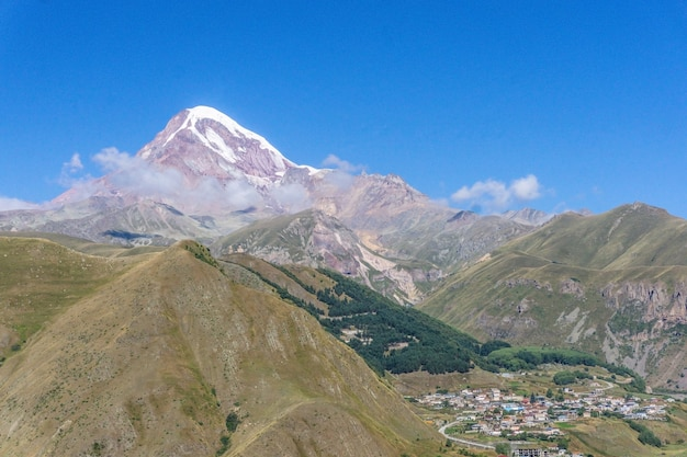 ジョージアのカズベク山。日当たりの良い夏の日の山の風景。