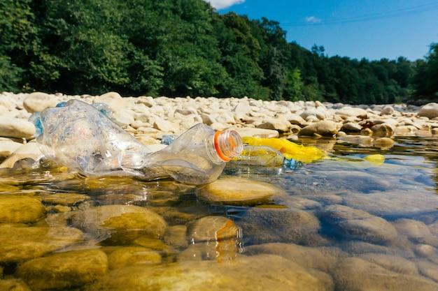 汚れたペットボトルとバッグ、水中のプラスチック