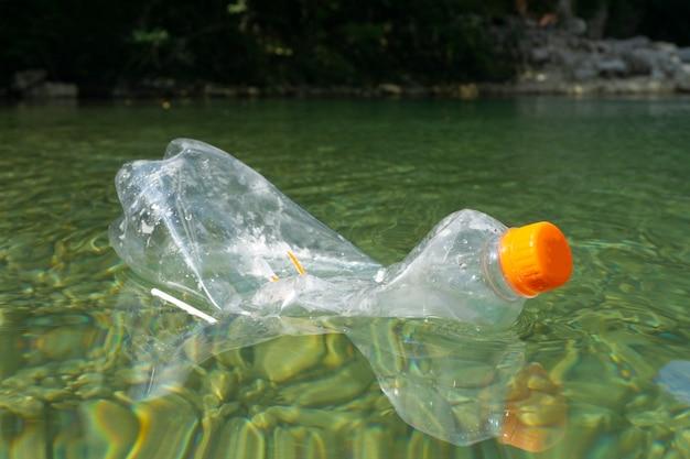 Грязные пластиковые бутылки в воде