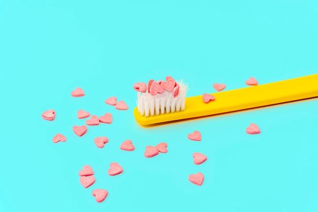 最小限のコンセプトが大好きです。ピンクとターコイズ色の歯ブラシとキャンディの心と明るいカラフルな背景。