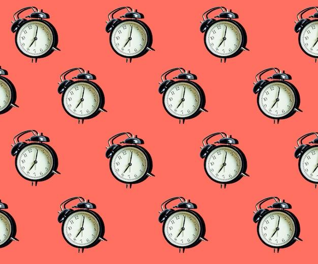 ピンクの最小限のパターンにビンテージの目覚まし時計。時間管理と時間の概念