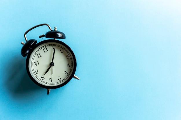 青いきれいな背景にビンテージの目覚まし時計。時間管理と時間の概念。