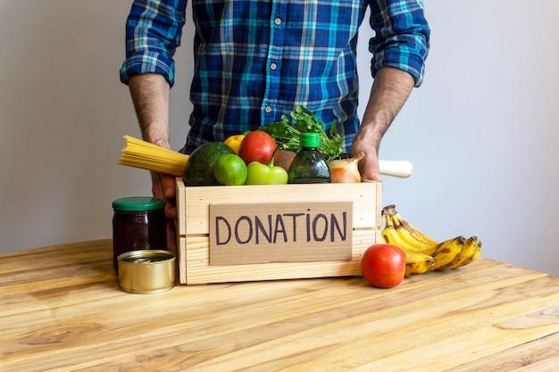 食品寄付のコンセプト。野菜、果物、その他の食糧を寄付するための募金箱を持った男
