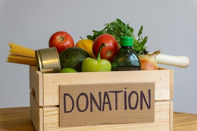 食品寄付のコンセプト。野菜、果物、その他の寄付用食品が入った募金箱