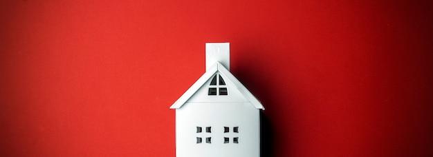 赤の背景に白の装飾的な家と最小限のクリスマスの背景。最小限のコンセプト。