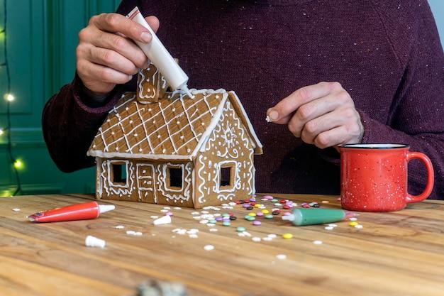 クリスマスのジンジャーブレッドの家を作ります。伝統的なクリスマスのベーキングとクッキー。