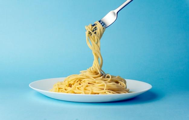 青色の背景に白いプレートにフォークでスパゲッティパスタ