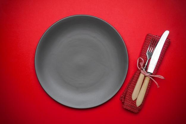 ナイフとフォークで赤い背景の空のプレート
