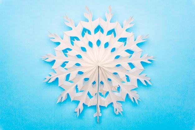 Белая снежинка из бумаги на синем фоне