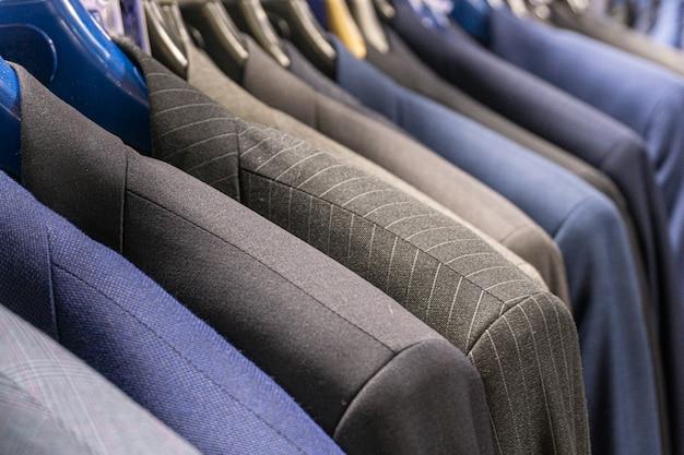 紳士服店の青とグレーの男性用ジャケット(スーツ)。メンズビジネススーツ