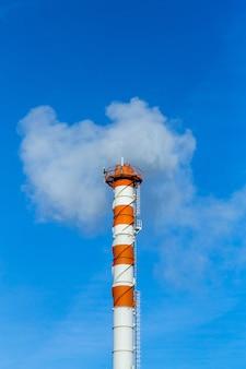 Загрязнение дымом. дымовые трубы на фоне голубого неба