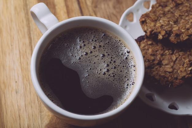 Утренний кофе с овсяным печеньем на деревянном столе. утренняя концепция кофе