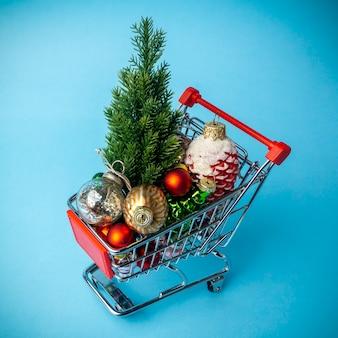 スーパーマーケットのカートの装飾とクリスマスツリー。クリスマスのショッピングと販売のコンセプト