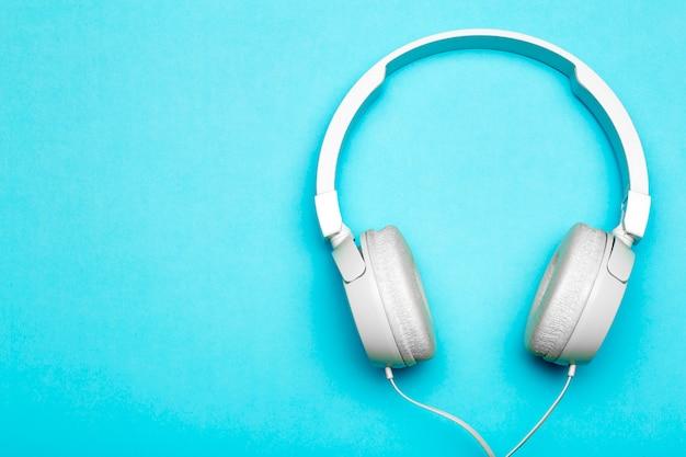 Музыкальные наушники на цветном синем фоне.
