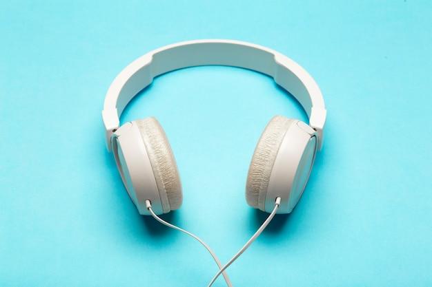 Музыкальные наушники на цветной синей поверхности