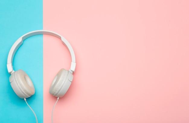Музыкальные наушники на цветном синем и розовом фоне