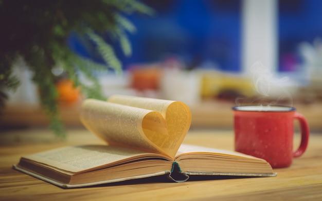 Открытая книга со страницей в форме сердца.