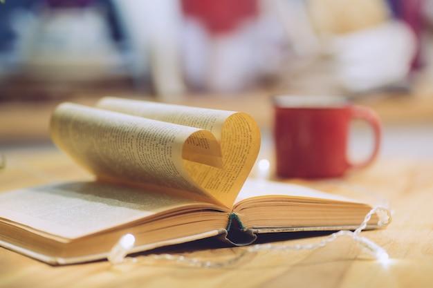 ハート形のページを開いた本。知識、教育または愛の概念