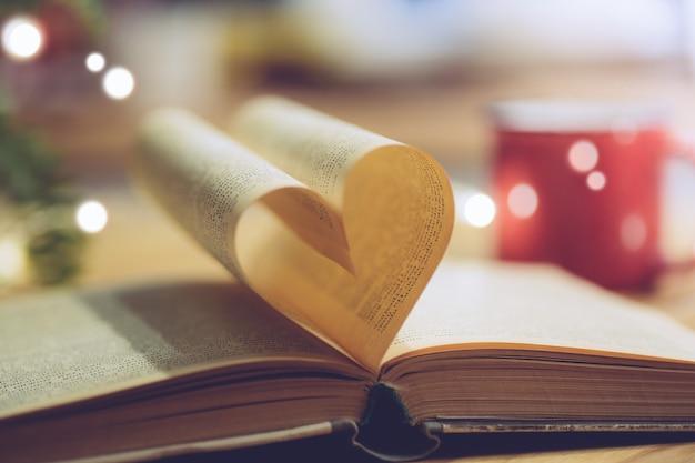 Открытая книга со страницей в форме сердца. знание, образование или концепция любви