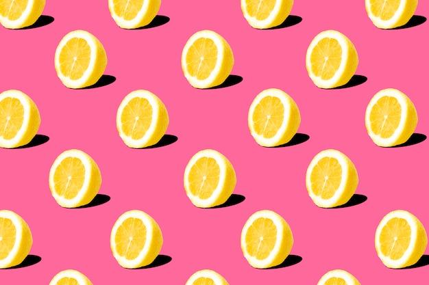 ピンクの背景に新鮮なレモン(レモン)パターン。最小限の概念夏の最小限の概念。フラットレイ