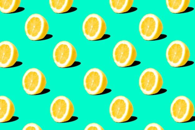 ターコイズグリーンの背景に新鮮なレモン(レモン)パターン。最小限の概念夏の最小限の概念。フラットレイ