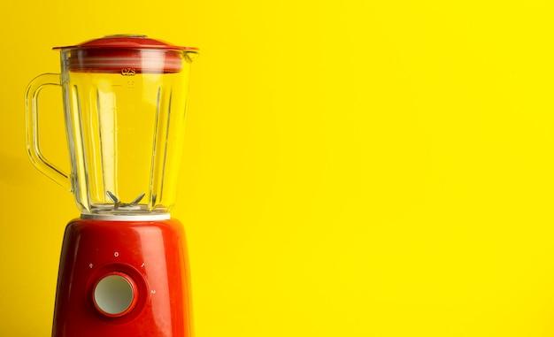 カクテルや自家製料理用のビンテージブレンダー。黄色の背景に赤のブレンダー。最小限のアートコンセプト、コピースペース