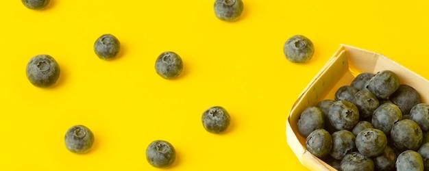 黄色のバナーの背景にブルーベリーの果実。色付きの黄色の背景にベリーの散乱。最小限の食べ物と夏のコンセプト
