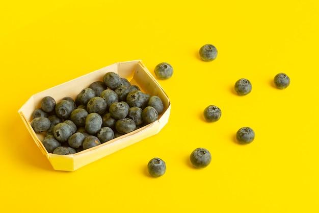 Ягоды черники на желтом фоне. россыпь ягод на цветном желтом фоне. минимальная еда и летняя концепция