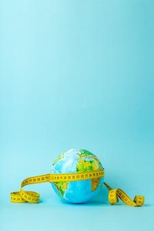 Большая дата, исследование, исследование, расстояния, измерения и концепция размера. глобус земли и измерительная лента на синем фоне. минимальный, копировать пространство