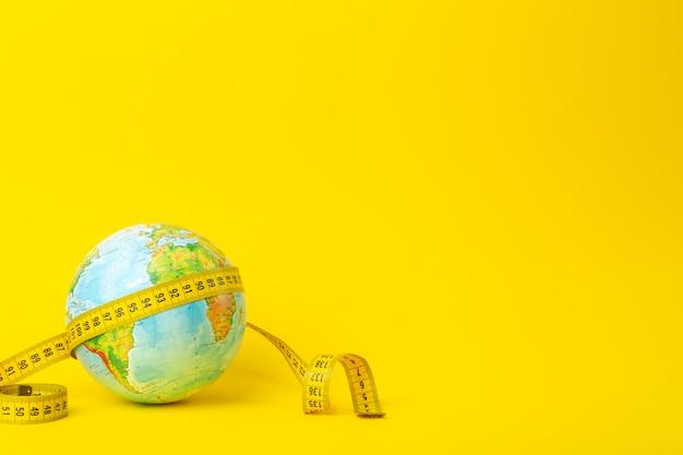 Большая дата, исследование, исследование, расстояния, измерения и концепция размера. земной шар и измерительная лента на желтом фоне. минимальный, копировать пространство