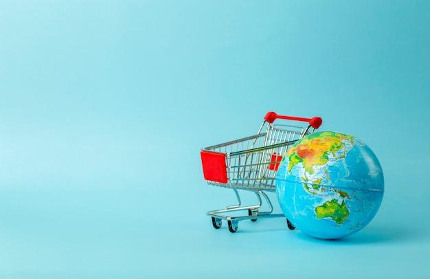世界販売とインターネット販売のコンセプト。青色の背景に地球とスーパーマーケットのカート。世界貿易と購入品の配送