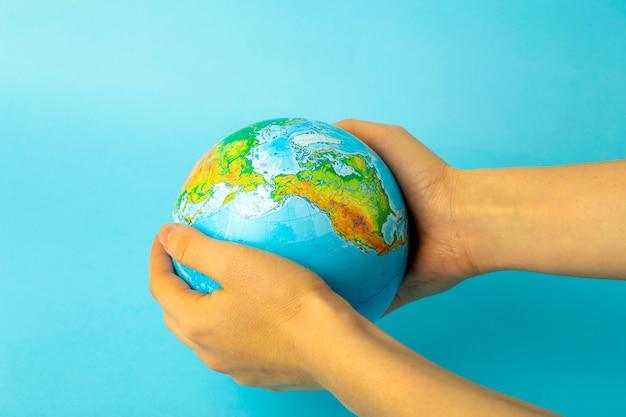 自然と地球の保全と保護。青い壁に女性の手で地球