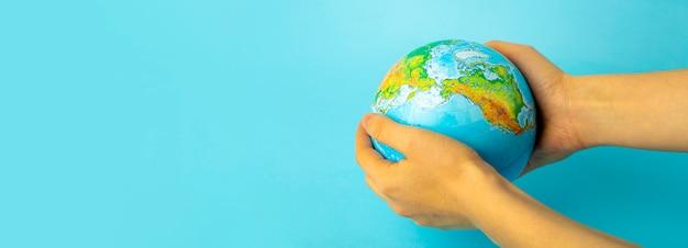 自然と地球の保全と保護。青色の背景に女性の手で地球。生態学および自然保護の概念
