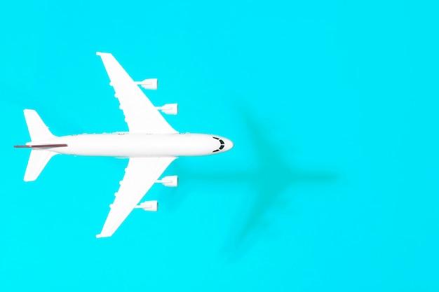最小限の背景を旅行します。空の色付きの背景で飛行中の模型飛行機。コピースペース