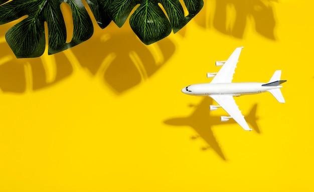 最小限の背景を旅行します。熱帯の葉の影で空の色付きの背景に飛行中の模型飛行機。コピースペース