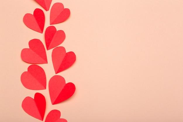 愛(バレンタインの日)背景や結婚式の背景。ピンクのパステル調の背景にピンクの紙の心。愛の概念