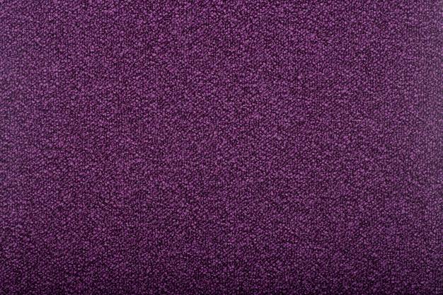 背景を覆うカーペット。バイオレット色のカーペットの模様と質感。コピースペース