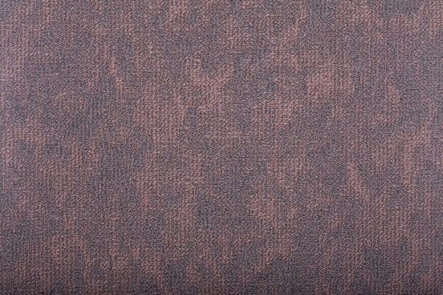 背景を覆うカーペット。暗い色のカーペットの模様と質感。コピースペース