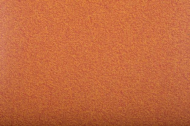 背景を覆うカーペット。モモ色のカーペットの模様と質感。コピースペース