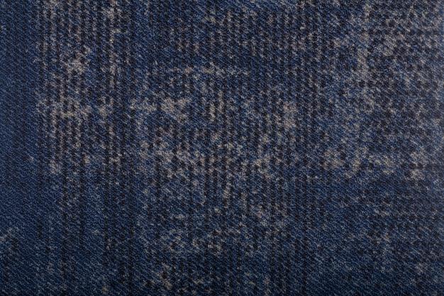 背景を覆うカーペット。濃い青色のカーペットの模様と質感。コピースペース